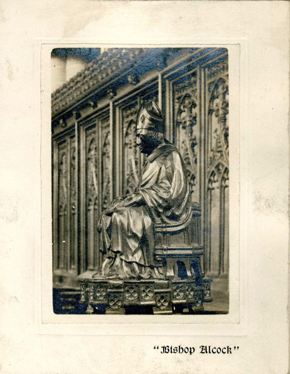 Here described as Bishop Alcock, a stall end in the College Chapel made in 1849 by James Rattee. It is a copy of one of the early 16th century figures from the Chapel which, at that date, was then in the parish church at Landbeach, Cambridgeshire. Christmas card 1910