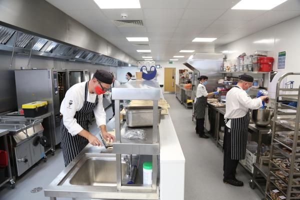 Chefs working in an industrial kitchen.