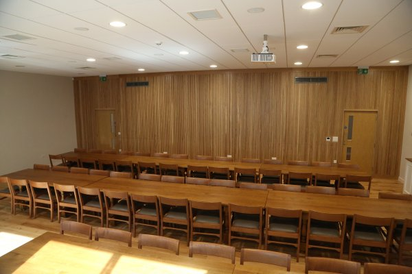 A large dining toom with two long runs of tables and chairs, and a feature wooden panelled wall.