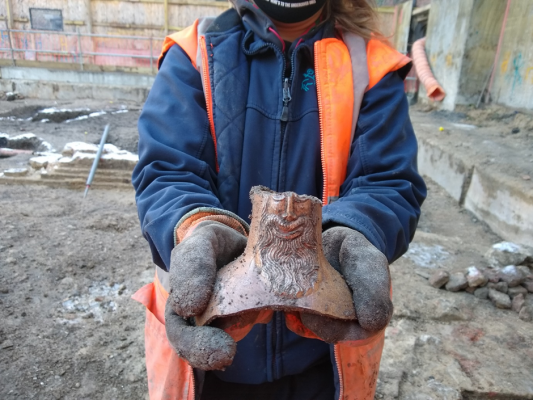 An archaeologist holding a shard of a Bellarmine jug, which resembles the bearded, grinning face and shoulders of a man.