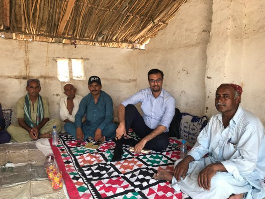 Photo of Dr Tayyab Safdar with local men during his fieldwork research