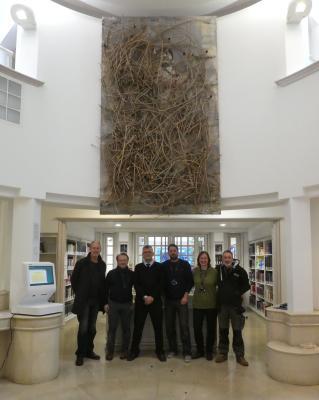 Installation team standing below artwork