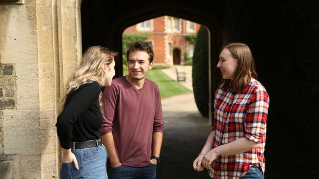 Image of Three students talking in an archway