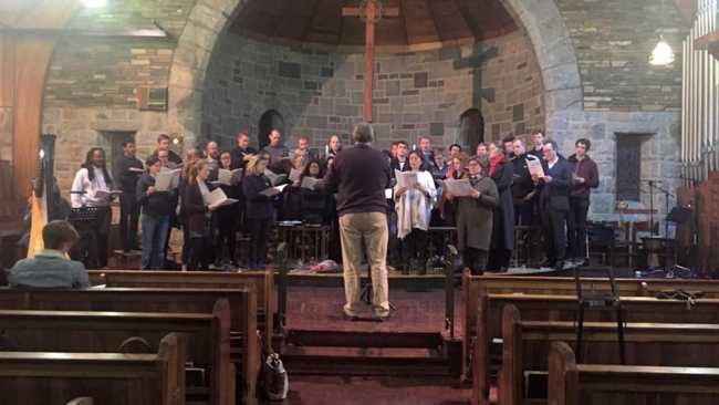 Photo of Approx 30 choir members in causal clothes standing in front of a church altar, holding music and being led by a conductor