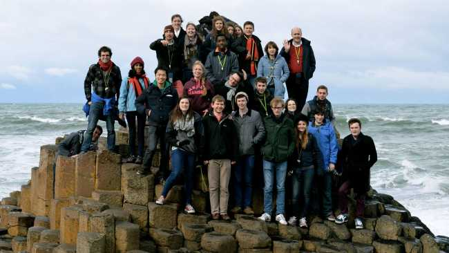 Photo of Choir posing for a group photo at Giant's Causeway
