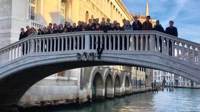 Photo of Choir members standing on a bridge over an Italian canal