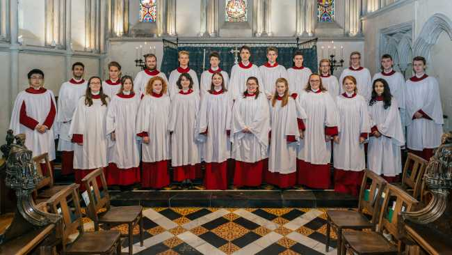Image of Choir members, wearing robes and standing in the College Chapel