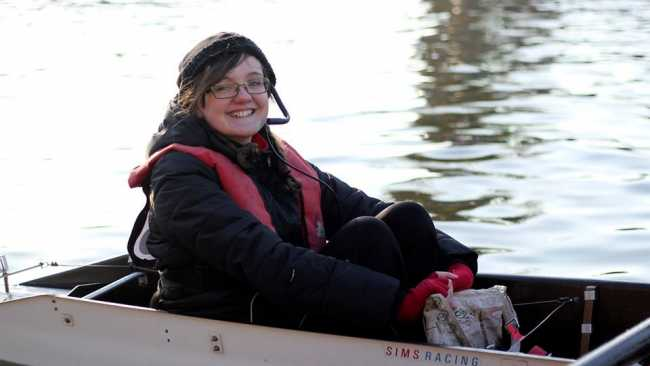 Image of Vicky sitting in a racing boat on a river